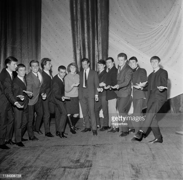 English music manager Brian Epstein pictured in centre with artists and bands he represents on stage at a venue in England in December 1963. Artists...