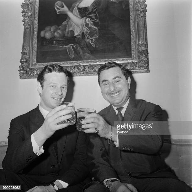 English music managers Brian Epstein on left and Vic Lewis share a toast with drinks after merging their pop music management agencies under the NEMS...