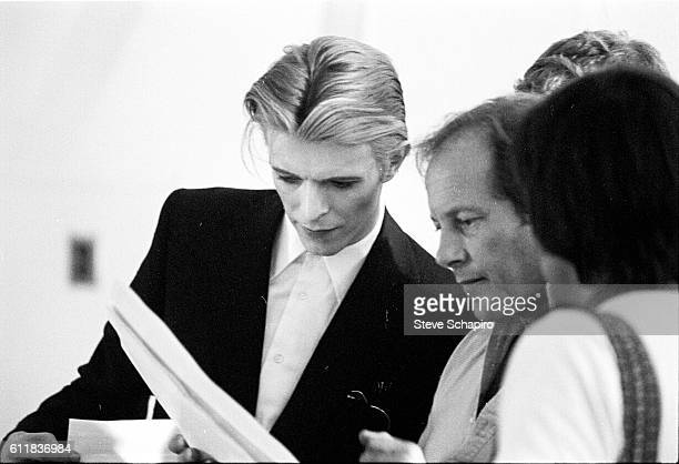 English musician and actor David Bowie leans in to read a paper held by director Nicolas Roeg during the filming of 'The Man Who Fell to Earth' , New...