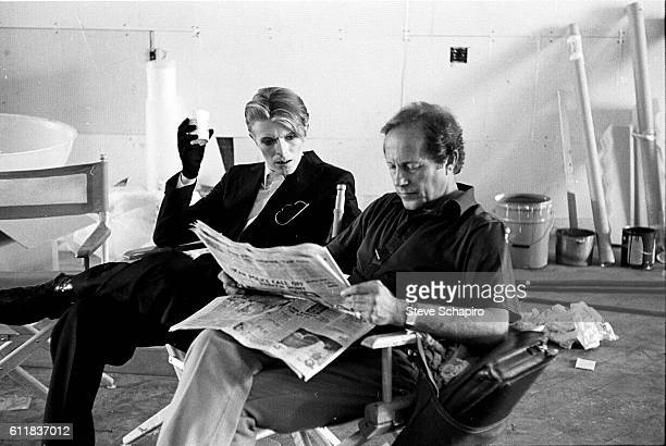 English musician and actor David Bowie sits beside director Nicolas Roeg, who reads a newspaper during a break in filming 'The Man Who Fell to Earth'...