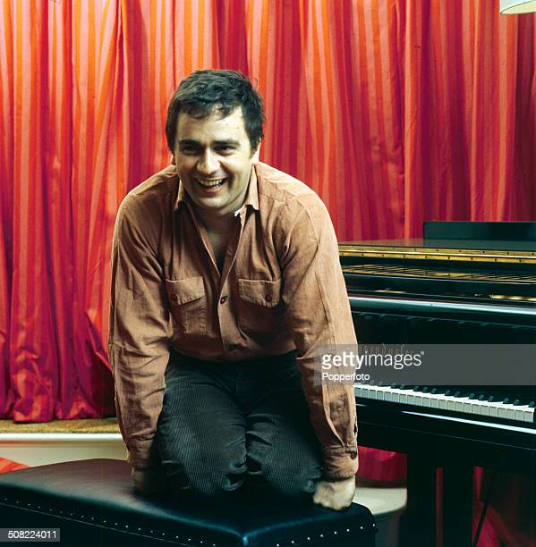 English musician and actor Dudley Moore posed on a piano stool in 1966