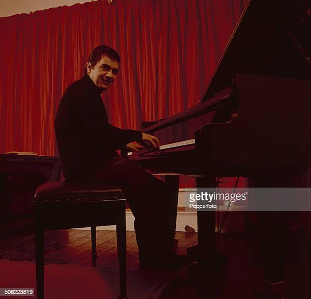 English musician and actor Dudley Moore posed sitting at a piano in 1966
