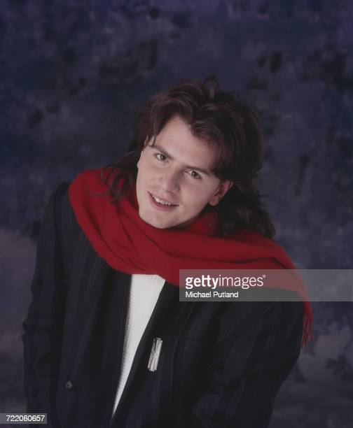 English musician and bass guitarist with Duran Duran John Taylor posed wearing a red scarf in 1985