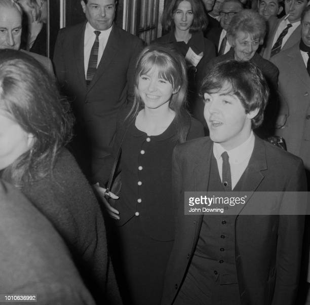 English musician and bass player with The Beatles Paul McCartney pictured with his girlfriend actress Jane Asher leaving the Comedy Theatre in London...