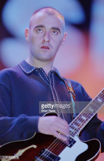 English musician and guitarist Paul 'Bonehead' Arthurs performs live on stage with rock group Oasis at Knebworth House in Hertfordshire, England on...