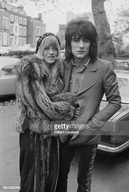English musician and guitarist with Faces, Ronnie Wood pictured with his wife Krissy on a street in London on 10th November 1973.