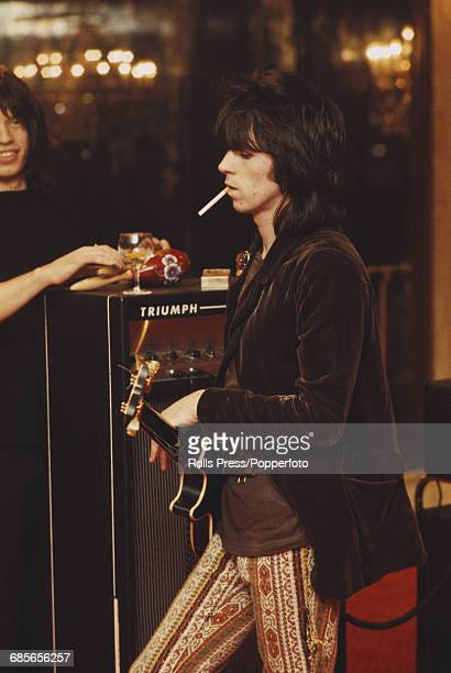 English musician and guitarist with Rolling Stones Keith Richards pictured smoking a cigarette with lead singer Mick Jagger during rehearsals for the...