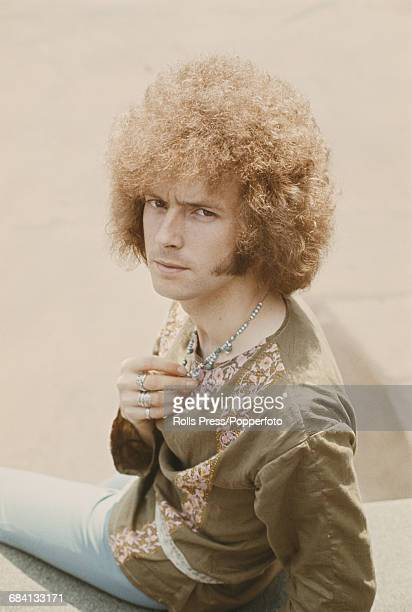 English musician and guitarist with the blues rock group Cream Eric Clapton posed wearing a kaftan style smock top and bead necklace in London in...