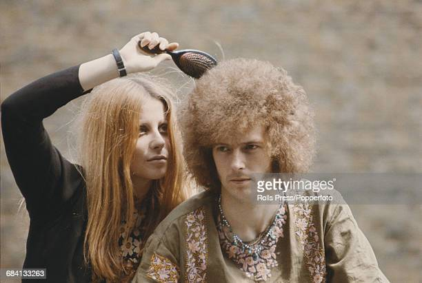 English musician and guitarist with the blues rock group Cream Eric Clapton pictured having his permed hair brushed by his girlfriend Charlotte...