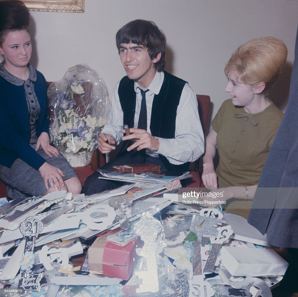 English musician and guitarist wth the Beatles, George Harrison (1943-2001) smokes a cigar whilst opening a multitude of birthday cards and greetings in celebration of his 21st birthday in February 1964.