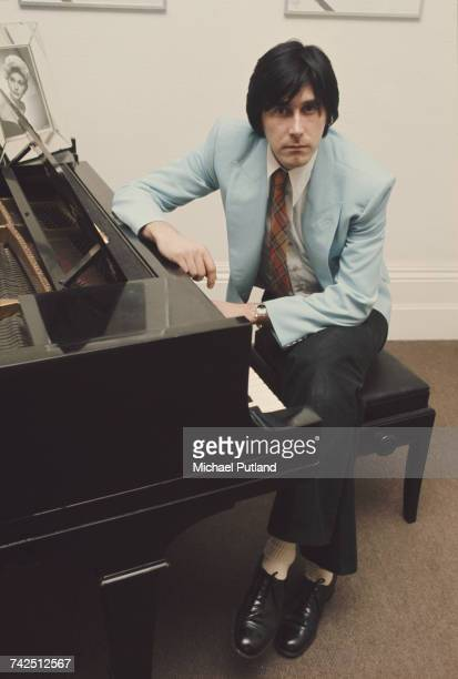 English musician and lead singer of Roxy Music Bryan Ferry pictured sitting at a piano at home in London on 10th January 1974