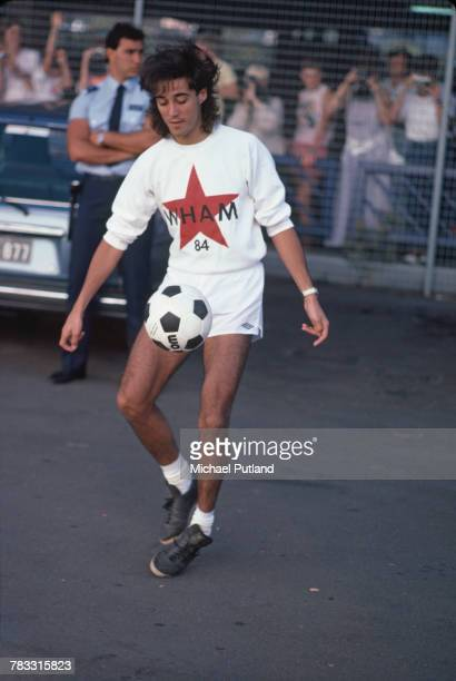 English musician and singer Andrew Ridgeley of Wham pictured kicking a football in Australia during the pop duo's 1985 world tour in January 1985...