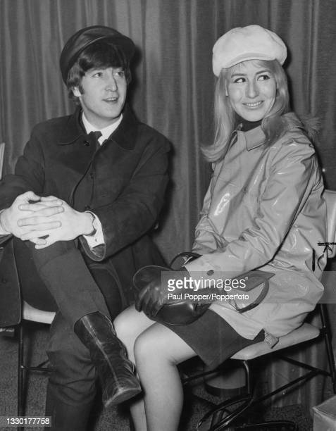English musician and songwriter John Lennon , guitarist with pop group The Beatles, seated with his wife Cynthia Lennon at London Airport on 7th...