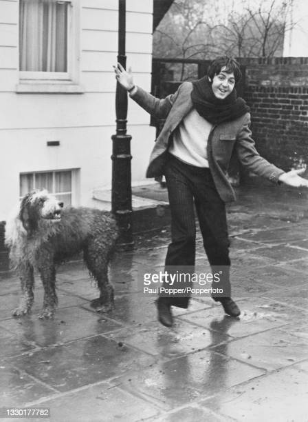 English musician and songwriter Paul McCartney, bass guitairst with The Beatles, takes his Old English Sheepdog Martha for a walk from his house in...