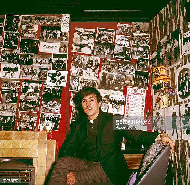 English musician Dave Clark drummer with The Dave Clark Five posed in a living room with walls covered in photographs of the group in 1964