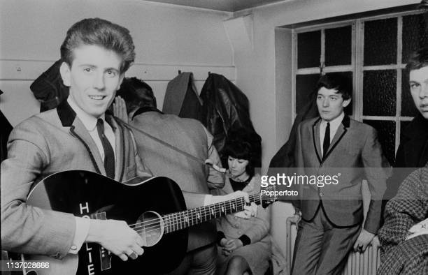 English musician Graham Nash singer and guitarist with The Hollies pictured with an acoustic guitar in a dressing room backstage during a tour by the...