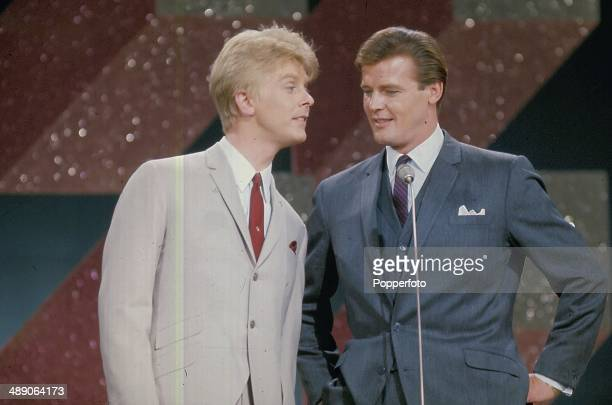 1968 English musician Joe Brown performs on stage with actor Roger Moore at the Palladium Show in London in 1968