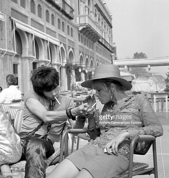 English musician Keith Richards litghting a cigarette to Anita Pallenberg sitting outside the Excelsior Hotel Lido Venice 1967