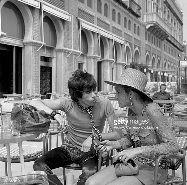 English musician Keith Richards talking to Anita Pallenberg sitting outside the Excelsior Hotel Lido Venice 1967