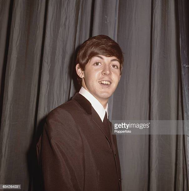 English musician singer and bass guitarist with The Beatles Paul McCartney pictured standing in front of a curtain backstage at a venue during the...