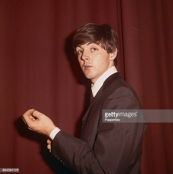English musician singer and bass guitarist with The Beatles Paul McCartney pictured standing in front of a red curtain backstage at a venue during...