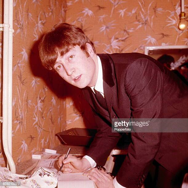 English musician singer and guitarist with The Beatles John Lennon pictured writing in a notebook in a dressing room backstage in 1963