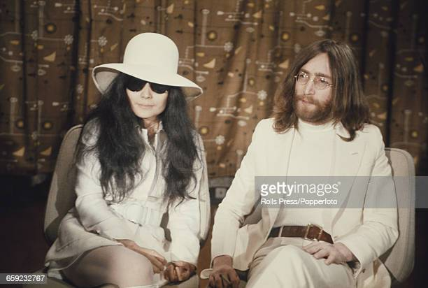 English musician singer and guitarist with the Beatles John Lennon pictured with his wife Yoko Ono at a press conference at Heathrow airport in...