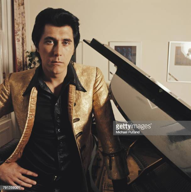 English musician singer and songwriter Bryan Ferry of Roxy Music pictured wearing a gold jacket at home in London circa 1972