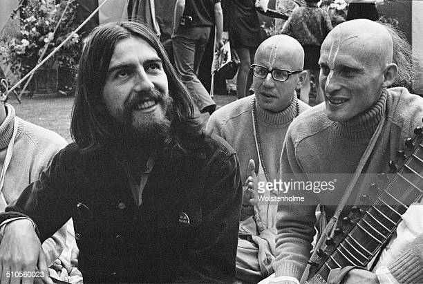 English musician, singer and songwriter, George Harrison sits with members of the Hare Krishna movement, 28th August 1969.