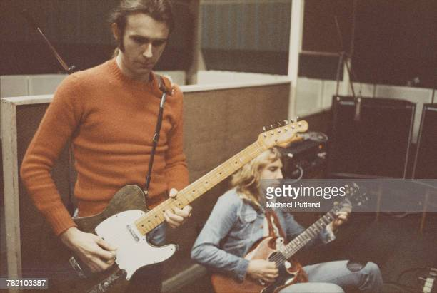 English musicians and guitarists with rock group Status Quo Francis Rossi and Rick Parfitt pictured playing a green Fender Telecaster and Gibson SG...