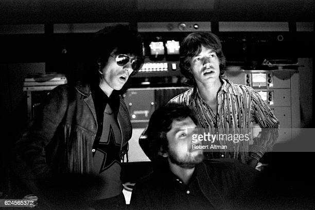 English musicians Keith Richards and Mick Jagger of the Rolling Stones along with producer Jimmy Miller work on the mixing of their Let It Bleed...