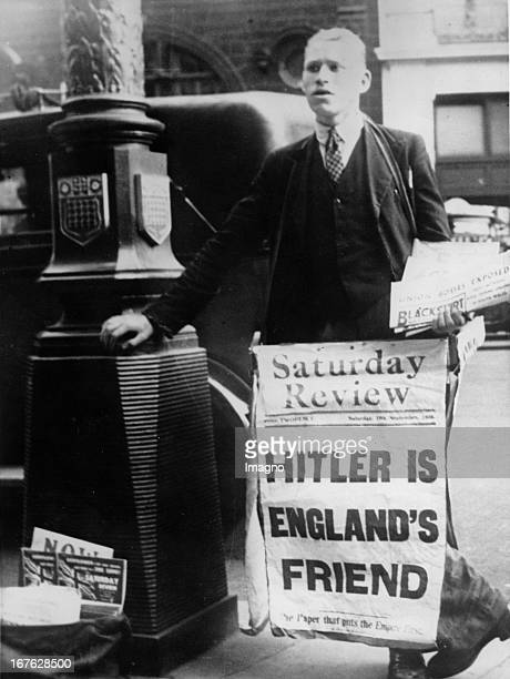 English newspaper vendor with a poster of the cover story in the Saturday Review The headline reads 'Hitler is England's Friend' Photograph...