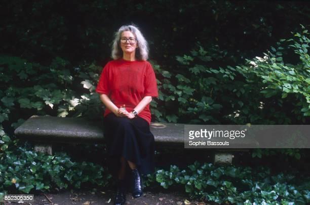 English novelist Angela Carter sitting on a park bench