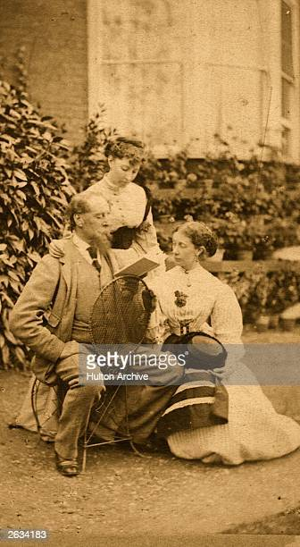 English novelist Charles Dickens seated backwards on a chair as he reads to his daughter and a companion