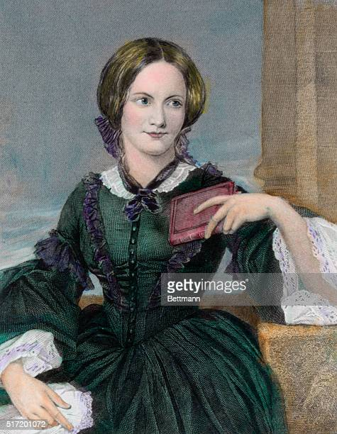 English novelist Charlotte Bronte seated with a small book in hand