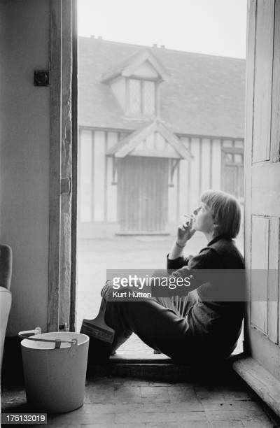 English novelist Emma Smith smokes a cigarette in her doorway after a day spent working on her cottage in StokebyNayland Suffolk England 29th April...