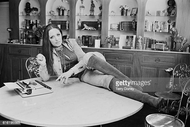 English novelist Jackie Collins poses with a typewriter UK 22nd March 1971