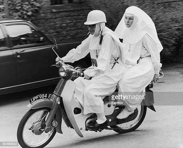 English nun Sister Joan Capistran taking Sister Mary Grace for a pillion ride on her 50cc Honda moped in the grounds of Ladywell Convent Godalming...