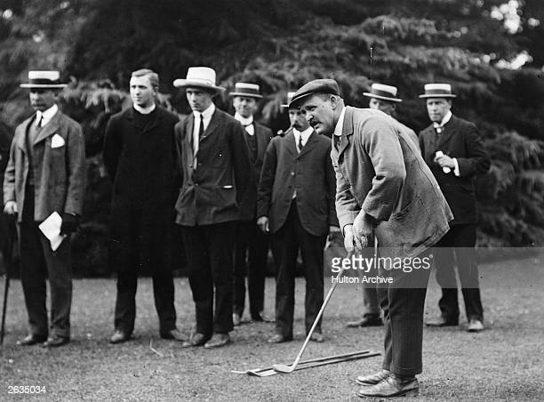 English Open Golf Champion John H Taylor is putting while a group of gentlemen look on John H Taylor won the British Open five times Original...