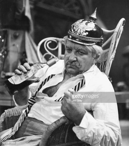 English opera singer Owen Brannigan wearing a World War I German helmet in a drunken scene from the Malcolm Williamson opera 'Our Man in Havana' at...
