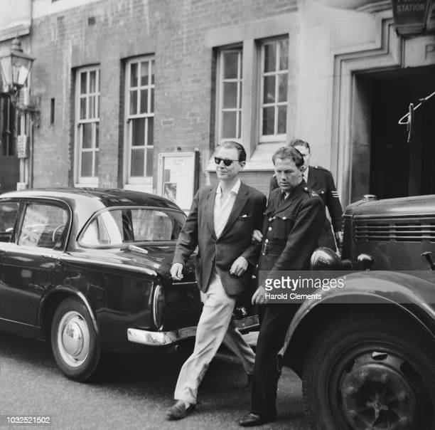 English osteopath and artist Stephen Ward mostly known for his involvement in the Profumo Affair is escorted out of a police station UK 11th June 1963