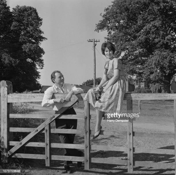 English osteopath and artist Stephen Ward with his friend Julie Gulliver sitting on a fence in the countryside UK 28th July 1963