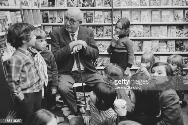 English painter artist and illustrator Edward Ardizzone talks with a group of young children in a bookshop in London on 15th October 1970