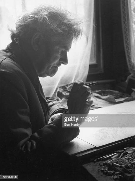 English painter war artist occultist and joint editor of the 'Golden Hind' art quarterly Austin Osman Spare at work at his flat in Brixton South...