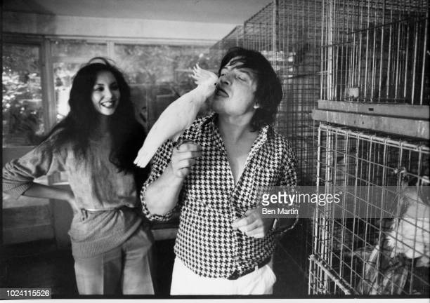 English photographer David Bailey kissing parrot with fashion model Marie Helvey London UK August 8 1977