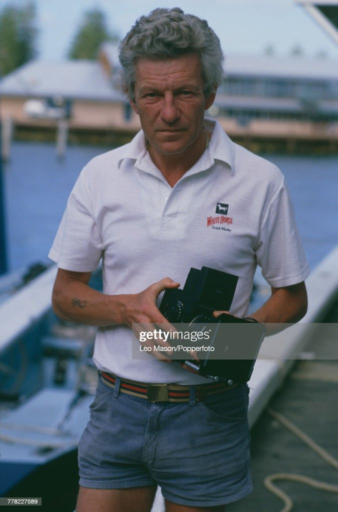 English photographer Patrick Anson, 5th Earl of Lichfield (1939-2005) pictured holding a Rolleiflex medium format SLR camera at Cowes on the Isle of Wight, England circa 1990.
