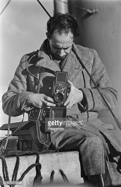 English photographer Reuben Saidman adjusts the settings to his Rolleiflex Automat twin-lens reflex camera on location to cover a story for...