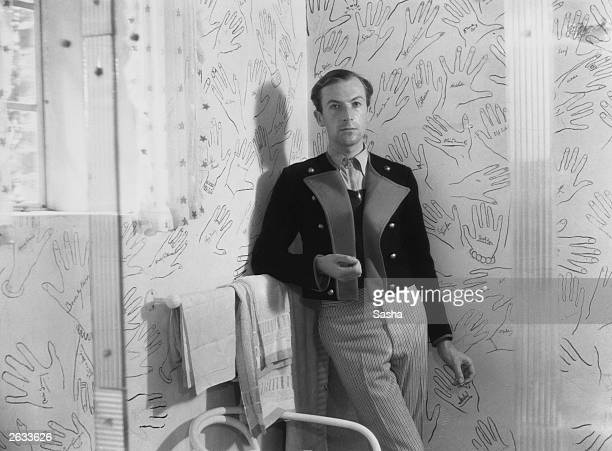English photographer Sir Cecil Walter Hardy Beaton in the bathroom of his home, 'Ashcombe' in Wiltshire, showing the walls decorated with autographed...