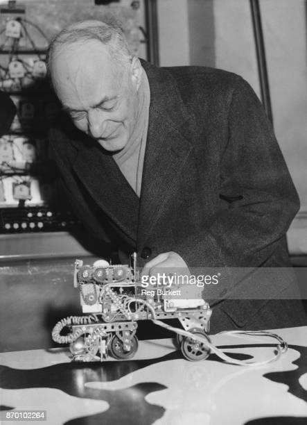English physical chemist and Nobel laureate Cyril Norman Hinshelwood President of the Royal Society examines a 'Learning Machine' at the Physical...