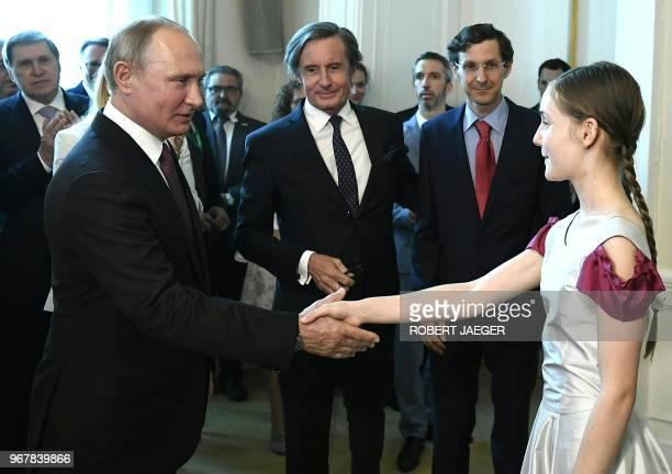 English pianist Alma Deutscher shakes hands with Russian President Vladimir Putin in Vienna Austria on June 5 2018 / Austria OUT